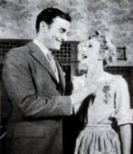 Richard Hart and Eva Gabor in The Happy Time: A love tap is administered by Uncle Desmonde as he pins one of his numerous medals on pretty Mignonette, a vaudeville acrobat turned maid, whose charms begin to affect him...