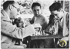 "Fred plays chess with son Doug, 22 (now also trying his hand at writing) while wife Hilda (""Bill"") kibitzes. Other son, Richard is, at 16, a talented magician. (Photo with original caption from Coronet magazine, 1956)."