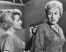 Constance Ford is holding the gun to Virginia's head in 'House of Women' (1962)