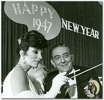 Joan Collins (Lady Daisy Frawley) waves a cigarette holder, attempting to learn Guy Lombardo's baton technique.