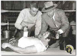 "POISONED PUNCH -- Manager Sam Hatter (Dane Clark, l.) and Doc Hatter (Lloyd Nolan) vainly try to revive Kid Hogan (heavyweight boxer Jerry Quarry) after a sparring match, in ""The Sunday Punch"" on the NBC Television network colorcast Sunday, Jan. 11 (8-9 p.m. NYT) 1976."