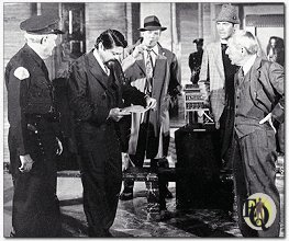 "Taped outline of where the body fell provides grim meeting place for principals in the ""Ellery Queen"" colorcast of ""The Pharoah's Curse"" The men are (from left) Wallace Rooney as museum guard, Ross Martin as museum director, Tom Reese as police sergeant Velie, Jim Hutton as Ellery Queen and David Wayne as Inspector Queen."